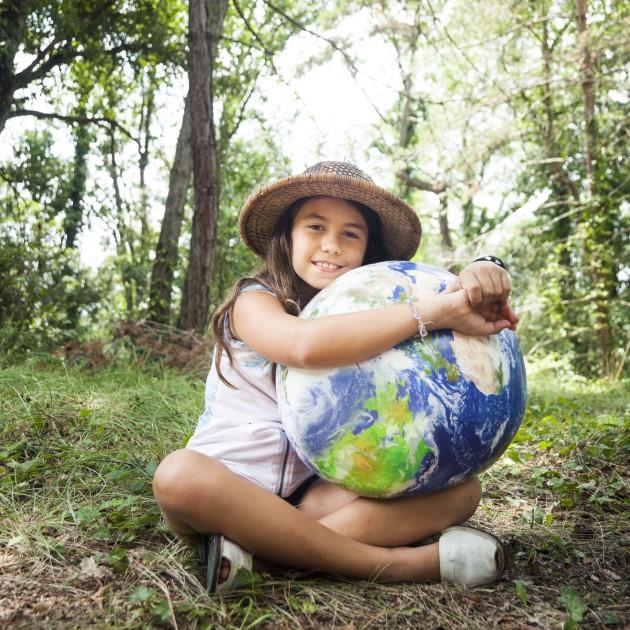 Ein Mädchen umarmt einen Globus
